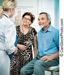 at the doctor's office - senior couple visiting a doctor at...
