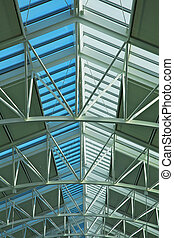 Glass skylight roof at airport showing blue sky with green...