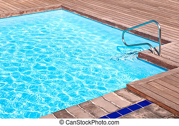Pool side - Wooden floor beside the blue swimming pool
