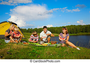 family picnic - outdoor portrait of happy families enjoying...
