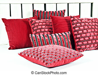 Combination of red and brown pillows on a bed with white...