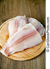Raw Fish - raw fish pangasius on a wood board