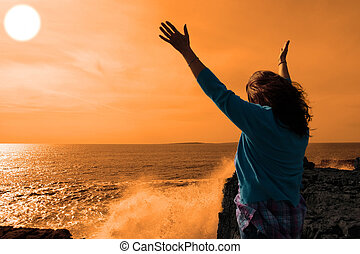 a lone woman raising her arms in awe at the powerful waves...