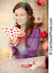 Valentines day - A young girl in restaurant holding...