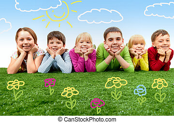 Friends - Group of happy children lying on a green grass