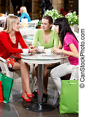 Girl communicating - Three young woman drinking coffee in...