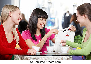 Girlfriends in cafe - Three young women sitting in cafe and...
