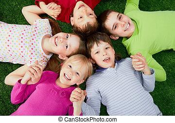 Happy kids - Image of happy friends lying on the grass and...