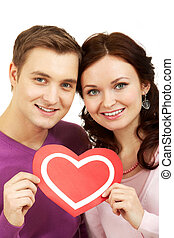 Lovers - Portrait of a young beautiful couple holding paper...