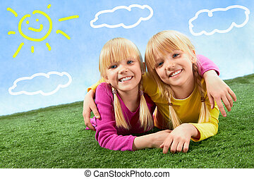 Twins  - Portrait of cute twins lying on a green grass