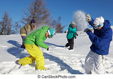 Playing snowfight - Four teenagers throwing snowballs...