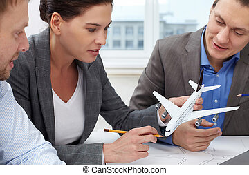 Invention of new plane - Three engineers looking at a small...