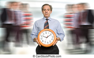 clock - mature handsome business man holding a clock