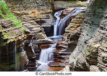 Watkins Glen waterfall in woods with rocks and stream in...