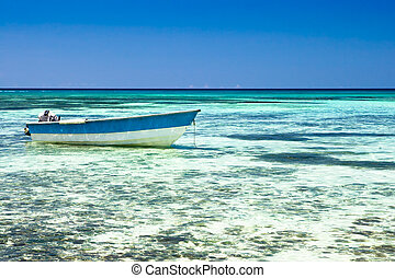White motor boat on a sand beach in the ocean with blue sky