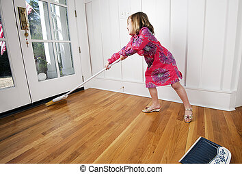 Young girl reaching to sweep wood floor by door. In motion,...