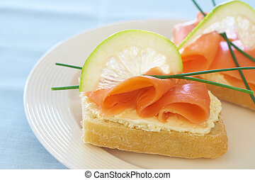 Smoked salmon and cream cheese on white bread with slice of...