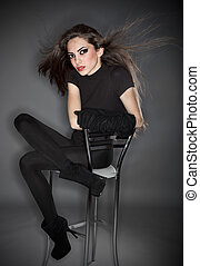 Young beautiful woman in black combi dress and velvet gloves holding her hairs, ring flash studio portrait