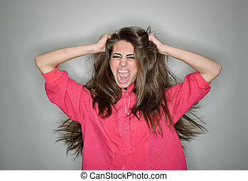 Screaming aggressive brunette woman dressed in pink blouse...