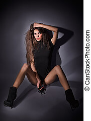 Young slim glamour lady with long hairs dressed in black combi dress sitting on the floor, dark key studio portrait