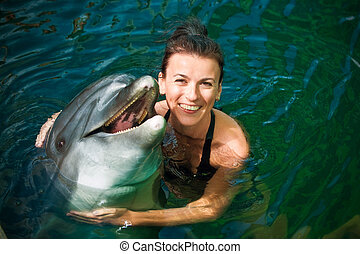 Girl and dolphin - Girl hugging a dolphin in the water