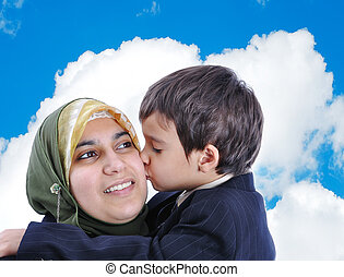 Muslim woman kissing her son