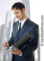 Portrait of a business man filling a form