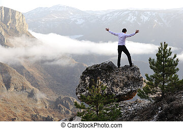 Man on top of mountain with open arms. Conceptual design.