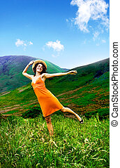 Woman outdoors in the countryside looking happy.