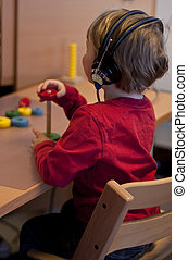 Small child (3 years old) taking a hearing test. A brick is...