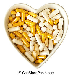Heart shaped bowl filled with medicine or diet supplements,...