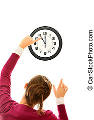 Changing time - A picture of young woman changing time on a...