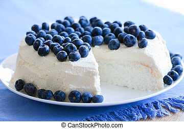 Angel food cake decorated with fresh blueberries and cream