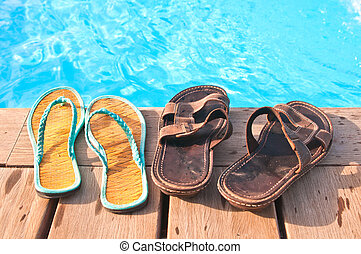 Two pairs (men's and woman's) of flip-flops by swimming pool...