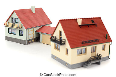 Models of two houses with garage for car on white background. Focus on the distant house.
