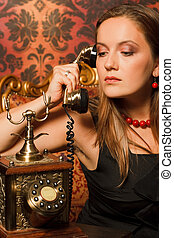 woman in black dress sitting on a vintage chair and talking on the old phone. holds the tube in his hands and looks down