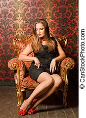 Woman in red shoes and a black dress sitting on a chair with...