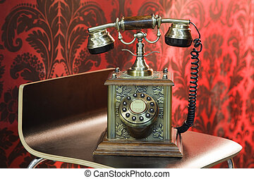 old phone made from metal stands on a wooden chair, red arnament. reflex on metal