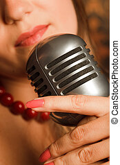 woman hugged hand vintage microphone placed on a rack. in the background lips. Focus on the microphone