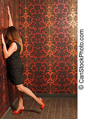 Woman in red shoes and black dress is pressed to the wall...
