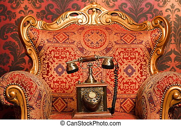 old phone is a red chair with gold accents, red vintage wallpaper. Focus on phone