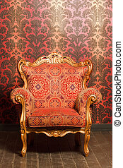 vintage red-yellow chair with gold accents standing beside the wall. wooden floor
