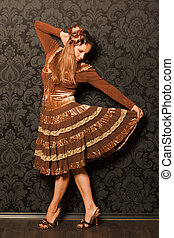 woman in a brown dress standing beside a wall. keeps the bottom of her skirt with his hand, looking at her skirt. black and gray pattern on the wallpaper wall.