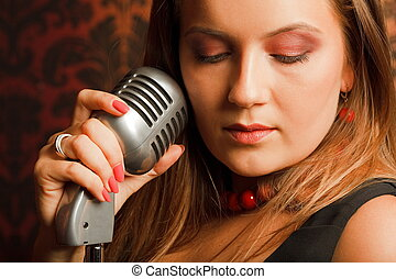 woman hugged hand vintage microphone placed on a stand. head turned to one side. eyes closed