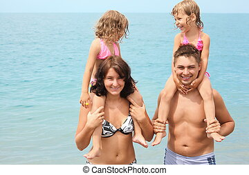 smiling mother and father near water with two little girls sitting on their necks.