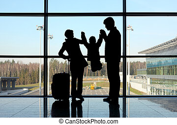 silhouette of parents holding their child for hands standing near window in airport