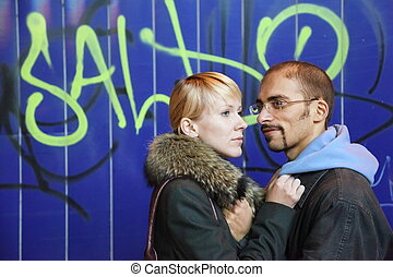 nightly street of coldly fall city. man and woman is staying near graffiti wall.