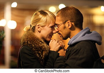 man and woman is cuddling in coldly nightly fall city. focus...