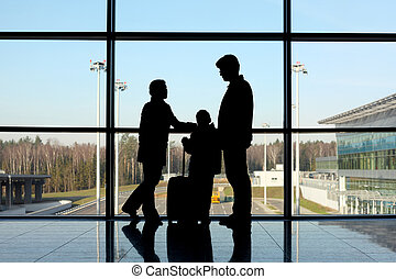 silhouette of family with luggage standing near window in airport