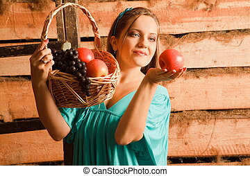 woman in a turquoise dress holding a basket of apples and grapes in their hands. holding an apple and looked at him. wooden wall